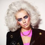 Portrait of young beautiful platinum blond woman with bold eyebrows and 80s  style makeup Stock Photo