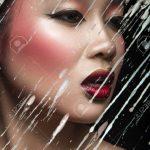 Schöne asiatische Mädchen mit hellen Make-up hinter Glas mit Tropfen Wachs.  Beauty Gesicht