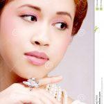 Recht asiatisches Mädchen mit Luxusschmuck und weichem Make-up