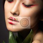 Fototapete Schöne asiatische Mädchen mit einem hellen Make-up-Kunst in  grünen Blättern.