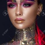 Beautiful girl with creative glitter makeup with sparkles, unusual  eyebrows. Beauty is an art
