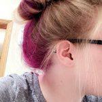 Purple hair dye under blonde messy bun -